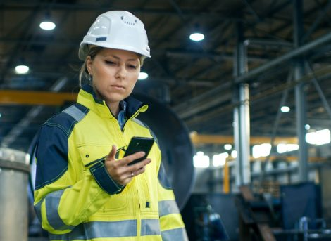 Female,Industrial,Worker,In,The,Hard,Hat,Uses,Mobile,Phone